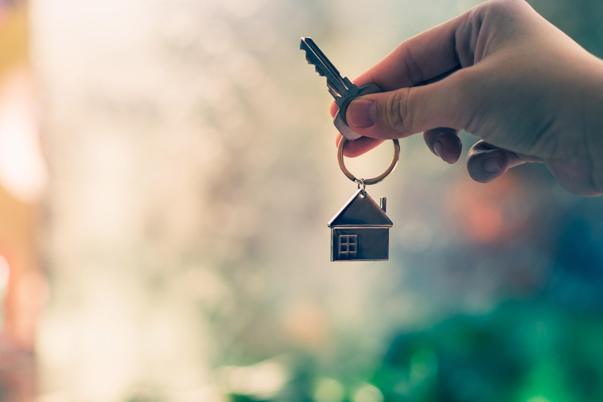 Hand hält Schlüssel + Schlüsselanhänger mit einem Haus